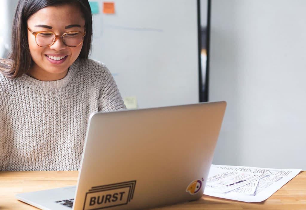 pessoa na frente do notebook sorrindo - Administrar Online - Terceirização do Financeiro - BPO Financeiro